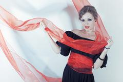 woman in black dress with red sash on light background - stock photo