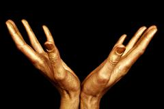 two male hands in gold paint isolated - stock photo
