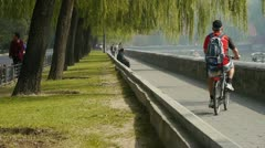 A man riding bicycle relying on willow river.yacht on lake. Stock Footage