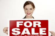 Stock Photo of attractive female realtor holds up the for sale sign
