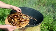 Hand take fresh smoked organic fish put wooden dish plate Stock Footage