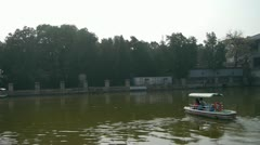 Tourists cruise ships on water,Dense willows by sparkling lake. Stock Footage