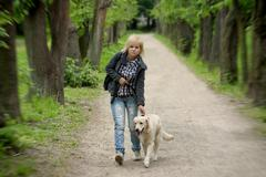 Blond woman walking with her golden retriever dog in the park Stock Photos