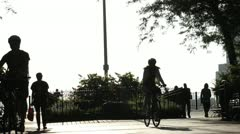 People in silhouette walk on the Brooklyn Heights Promenade Stock Footage