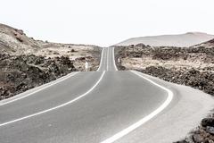 Empty road crossing an arid mountain, lanzarote, canary islands, spain Stock Photos