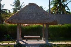 tropical summerhouse with bench - stock photo