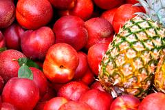 many ripe nectarines, and pineapple - stock photo