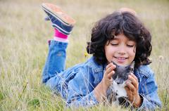 very cute little girl with cat on meadow - stock photo