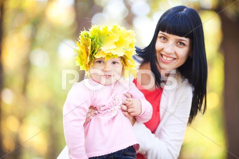 Stock photo of beautiful young mother holding her daughter in a wreath of maple leaves