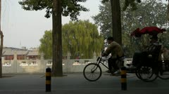 Tricycle carrying tourists sightseeing in Beijing's tree hutong alley tour. Stock Footage