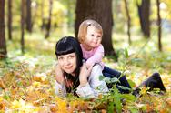 Beautiful young mother and her daughter lying on the autumn leaves Stock Photos