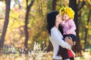 Beautiful young mother holding her daughter in a wreath of maple leaves Stock Photos
