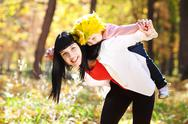 Beautiful young mother holding her daughter in a wreath of maple leaves on ba Stock Photos