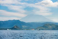 big volcano rise over the island and sea - stock photo