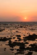 Warm tropical sunset over mountaint and sea on front Stock Photos