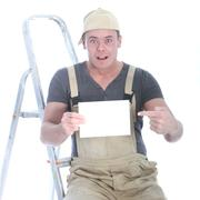 shocked handyman with blank sign - stock photo