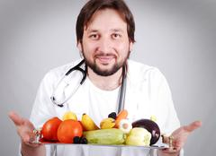 young male doctor advising healthy natural food - stock photo