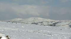 Pan of snow covered Dartmoor hills overlooking widecombe Stock Footage