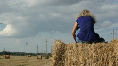 Sexy young blonde woman fun sit straw bale agriculture field Stock Footage