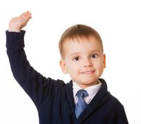 Small schoolboy raises his hand for answer Stock Photos