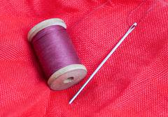 Needle and thread on a red background Stock Photos