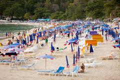 Thailand, beach: tourists, sunbeds and umbrellas Stock Photos