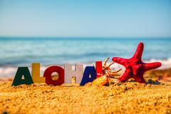 Wooden colorful word 'aloha' on the sand Stock Photos