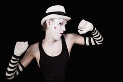 ape mime in striped gloves and white hat on black background - stock photo