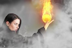 Magician woman with a fire ball in her hands Stock Illustration