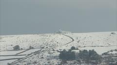 Road running from snowy Dartmoor Tor Stock Footage