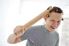 Senior woman with a rolling pin and curlers on hair Stock Photos