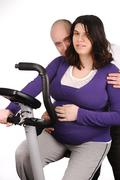 pregnant woman on treadmill with her husband - stock photo