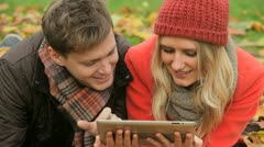 Couple surfing wireless tablet in park in Autumn - stock footage