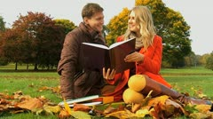Caucasian students studying among country park leaves Stock Footage