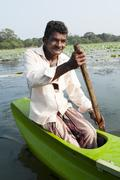 Smiling asian man row a small traditional boat Stock Photos