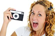 Stock Photo of an excited teenage girl shouting holding a retro camera in hand