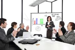 Business woman making the presentation and receiving applause Stock Photos