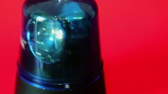 Bulb spins in blue flasher which moves slowly isolated on red Stock Footage