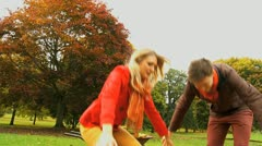 Laughter in the park Fall time young couple playing Stock Footage