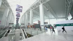 Many passengers walk in huge hall of airport Stock Footage