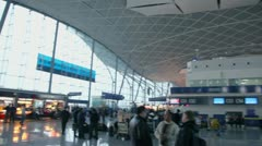 Lot of people stand near cashoffice in hall of Urumchi airport Stock Footage