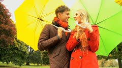 Couple sheltering from weather in the park in Autumn - stock footage