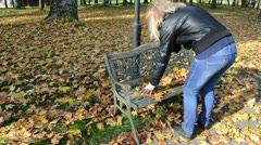 cute blond woman jeans clean autumn maple tree leaves park bench - stock footage