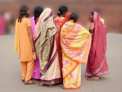 indian women in colorful saris approach the red fort's main gate - stock photo