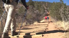 Man with hiking poles walking up incline Stock Footage