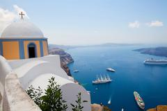old church dome and view of boats in santorini - stock photo