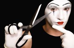 mime with scissors on  black background - stock photo