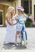 mother parent & girl child learning to ride bike - stock photo