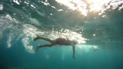 7 years old boy swims in the sea, underwater view. WS Stock Footage