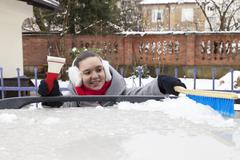 Removing ice and snow from the car roof Stock Photos